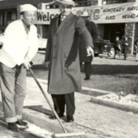 Honorary Mayor Bing Crosby sweeping Elko street supervised by Mayor Dave Dotta, 1948