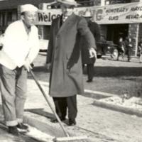 Honorary Mayor Bing Crosby sweeping Elko street supervised by Mayor Dave Dotta, 1948